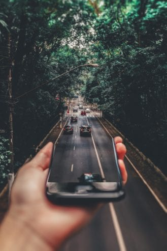 person holding phone and screen transforms to street in real life
