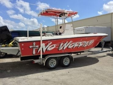 fishing boat with red wrap that says no worries by Fantasea Media