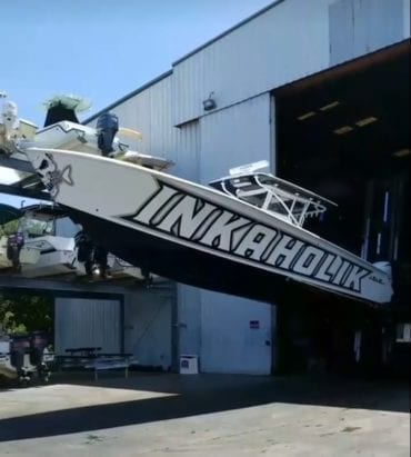 white boat with black decals that say inkaholik on the side by Fantasea Media