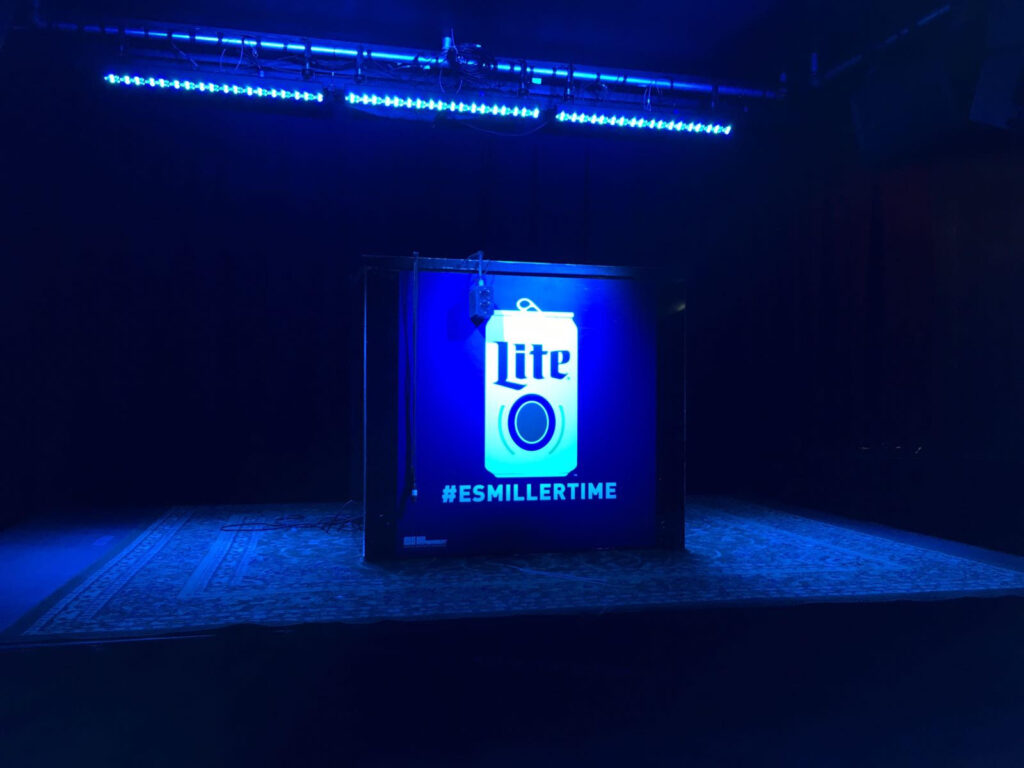backlit miller lite preforated wrap with light shining through event stage wrap design by fantasea media